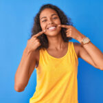 Brunette woman points to her healthy smile while wearing a yellow tanktop against a blue background