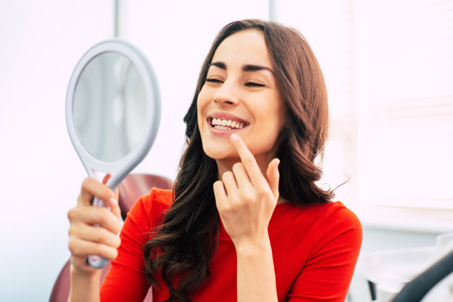 Smiling brunette woman holding a mirror to view her Botox treatment.